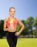 Smiling sporty woman with protein shake bottle Stock Photos