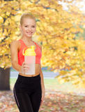 Smiling sporty woman with protein shake bottle Stock Photography