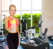 Smiling sporty woman with protein shake bottle Royalty Free Stock Images