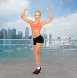 Smiling sporty woman showing her biceps Royalty Free Stock Photography