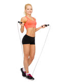 Smiling sporty woman with with skipping rope Stock Images