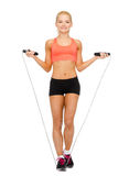 Smiling sporty woman with with skipping rope Stock Photos