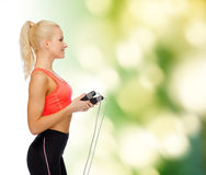 Smiling sporty woman with skipping rope Stock Image