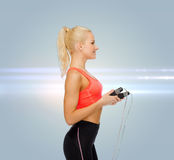 Smiling sporty woman with skipping rope Royalty Free Stock Images