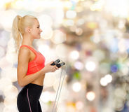 Smiling sporty woman with skipping rope Royalty Free Stock Photography