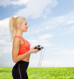 Smiling sporty woman with skipping rope Royalty Free Stock Photo