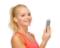 Smiling sporty woman with smartphone and earphones Royalty Free Stock Image