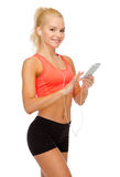 Smiling sporty woman with smartphone and earphones Royalty Free Stock Images