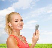 Smiling sporty woman with smartphone and earphones Royalty Free Stock Photography