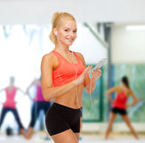 Smiling sporty woman with smartphone and earphones Stock Photos