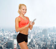 Smiling sporty woman with smartphone and earphones Stock Image