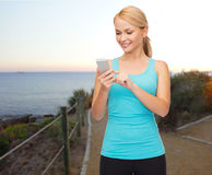 Smiling sporty woman with smartphone outdoors Royalty Free Stock Images