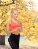 Smiling sporty woman with smartphone Royalty Free Stock Image