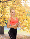 Smiling sporty woman with smartphone Stock Photos