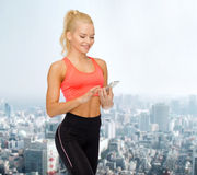 Smiling sporty woman with smartphone Royalty Free Stock Images