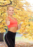 Smiling sporty woman with smartphone Royalty Free Stock Photos