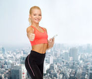 Smiling sporty woman with smartphone Stock Image