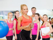 Smiling sporty woman with smartphone Stock Images