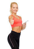 Smiling sporty woman with smartphone Royalty Free Stock Photo
