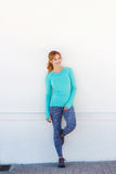 Smiling sporty woman standing by white wall Royalty Free Stock Photography