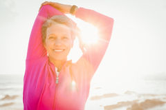 Smiling sporty woman stretching arms at promenade Royalty Free Stock Images