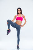Smiling sporty woman stretching leg Stock Photo
