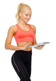 Smiling sporty woman with tablet pc computer Royalty Free Stock Photography