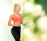 Smiling sporty woman with tablet pc computer Stock Photos