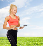 Smiling sporty woman with tablet pc computer Royalty Free Stock Images