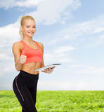 Smiling sporty woman with tablet pc computer Stock Photo