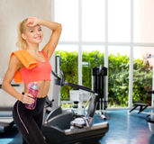 Smiling sporty woman with towel and water bottle Royalty Free Stock Image