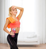 Smiling sporty woman with towel and water bottle Royalty Free Stock Photography