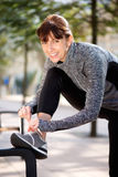 Smiling sporty woman tying shoelace outside Stock Images