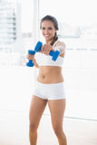 Smiling sporty woman using dumbbells Stock Photo