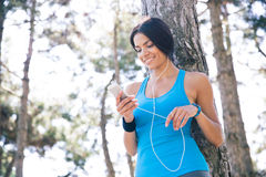 Smiling sporty woman using smartphone outdoors royalty free stock photo