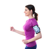 Smiling sporty woman in violet T-short over white isolated background. Smiling and moving, running sporty woman in violet T-short with smart phone device and Royalty Free Stock Photography