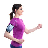 Smiling sporty woman in violet T-short over white isolated background. Smiling and moving, running sporty woman in violet T-short with smart phone device and Royalty Free Stock Image