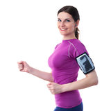 Smiling sporty woman in violet T-short over white isolated background. Smiling and moving, running sporty woman in violet T-short with smart phone device and Stock Photos