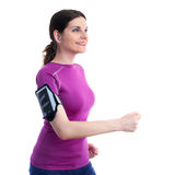 Smiling sporty woman in violet T-short over white isolated background. Smiling and moving, running sporty woman in violet T-short with smart phone device and Stock Image