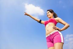 Smiling sporty woman watching and pointing far away Royalty Free Stock Photography