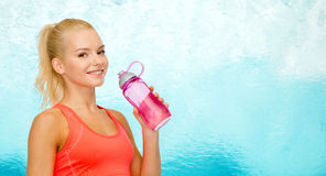 Smiling sporty woman with water bottle Stock Images