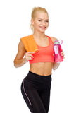 Smiling sporty woman with water bottle and towel Royalty Free Stock Images