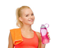 Smiling sporty woman with water bottle and towel Royalty Free Stock Photography