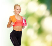 Smiling sporty woman with water bottle and towel Stock Images