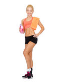 Smiling sporty woman with water bottle and towel Stock Photo