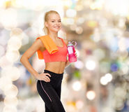 Smiling sporty woman with water bottle and towel Royalty Free Stock Photo