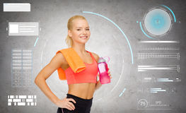 Smiling sporty woman with water bottle and towel Stock Photography