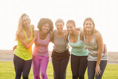 Smiling sporty women with arms around each other Royalty Free Stock Photography