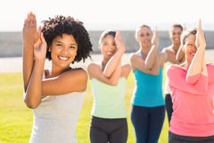 Smiling sporty women doing eagle pose in yoga class Royalty Free Stock Photography