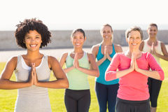 Smiling sporty women doing prayer position in yoga class Stock Image